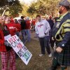 Garry Canaday, far right, is a lifelong Notre Dame fan. For his birthday, his best friend, Brook Bullock,Oklahoma City, second from left, an avid Sooners fan, purchased tickets to Saturday\'s OU-Notre Dame football game. Canaday, who lives in Tonkawa, wore a kilt to the game. He said he is Scottish and the kilt represents his clan\'s tartan. At left is OU freshman Brittany Boren of Ft. Worth, who teased Canaday by showing him the sign she made. ESPN broadcast their weekly pre-game sports show, GameDay, from the the campus of the University of Oklahoma, Saturday morning, Oct. 27, 2012. The network\'s broadcast few is in Norman for the OU - Notre Dame football game Saturday night. Several thousand OU fans and a smattering of Notre Dame supporters , many carrying homemade signs, crowded around the stage to watch the live broadcast. Photo by Jim Beckel, The Oklahoman