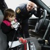 Kaelynn Fenimore, 5, uses the outside speaker of Moore Police officer Trevor Troxell\'s police car before her ride to the store during the Second Annual Shop with a Cop on Saturday, Dec. 8, 2012 in Moore, Okla. Photo by Steve Sisney, The Oklahoman