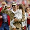 Photo - A military servicemman surprises his family on the field during the college football game between the University of Oklahoma Sooners (OU) and the Iowa State University Cyclones (ISU) at Gaylord Family-Oklahoma Memorial Stadium in Norman, Okla. on Saturday, Nov. 16, 2013. Photo by Steve Sisney, The Oklahoman