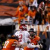 Oklahoma\'s Landry Jones (12) is hit by Oklahoma State\'s Alex Elkins (37) as he fumbles during the Bedlam college football game between the Oklahoma State University Cowboys (OSU) and the University of Oklahoma Sooners (OU) at Boone Pickens Stadium in Stillwater, Okla., Saturday, Dec. 3, 2011. Photo by Bryan Terry, The Oklahoman