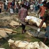Workers carry unclaimed bodies from the garment factory building collapse in preparation for a mass burial on Wednesday May 1, 2013 in Dhaka, Bangladesh. Several hundred people attended a mass funeral in a Dhaka suburb for 18 unidentified workers who died in the building collapse last week last week in the country\'s worst industrial disaster, killing at least 402 people and injuring 2,500. The bodies, rotting in the spring heat, were brought to the graveyard on the back of a flatbed truck.(AP Photo/Wong Maye-E)