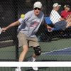 In this Monday, Dec. 3, 2012 photo, Del Teter competes in a game of pickleball at Sun City West senior community in Surprise, Ariz. A hybrid of tennis, badminton and table tennis, pickleball is played on a court a quarter the size of a tennis court, There\'s usually four players, two each side on a team, playing over a net slightly lower than in tennis, using rackets that look like a beefed-up version of a beach paddleball paddle to hit a whiffle ball that\'s slightly harder than the play-in-the streets variety. (AP Photo/Matt York)