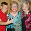 Cheyenne Middle School students helped with arrangements for Touchmark at Coffee Creek\'s \'senior\' prom recently. Residents shared their prom pictures. Student Shane Shipman shows an event photo he took to Melne Lyons, and Bettye Brown, right.