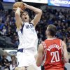 Photo - Dallas Mavericks forward Dirk Nowitzki (41), of Germany, shoots against Houston Rockets forward Donatas Motiejunas (20), of Lithuanian, during the first half of an NBA basketball game Wednesday, Jan. 29, 2014, in Dallas. (AP Photo/LM Otero)
