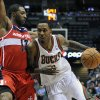 Washington Wizards\' A.J. Price (12) defends as the Milwaukee Bucks\' Brandon Jennings drives to the basket during the second half of an NBA basketball game Monday, Feb. 11, 2013, in Milwaukee. The Wizards defeated the Bucks 102-90. (AP Photo/Jim Prisching)