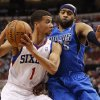 Photo - Philadelphia 76ers' Michael Carter-Williams, left, drives to the basket with Dallas Mavericks' Vince Carter, right, defending during the first half of an NBA basketball game, Friday, Feb. 21, 2014, in Philadelphia. (AP Photo/Chris Szagola)