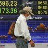 A man walks in front of the electronic stock board of a securities firm showing Japan\'s Nikkei 225 index falling 173.36 points to 8596.23 in Tokyo, Wednesday, Oct. 10, 2012. Worries about Europe\'s debt crisis, signs of weak global growth and expectations of lower U.S. corporate earnings sent most Asian stock markets down Wednesday. (AP Photo/Itsuo Inouye)