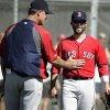 Photo - Boston Red Sox manager John Farrell, left, gives Red Sox second baseman Dustin Pedroia, right, a pat on the stomach during spring training baseball practice, Monday, Feb. 17, 2014, in Fort Myers, Fla. (AP Photo/Steven Senne)