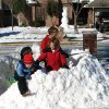 From left, Joey, Mac (partially obscured), Lucy and Will Mecoy take haven inside their freshly built snow fort in Edmond. In the background is the neighbor\'s 10-foot OU snowman. Community Photo By: Mishelleen Mecoy Submitted By: Don, Edmond