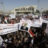 Shiite demonstrators chant pro-government slogans and wave national flags, to show support for Prime Minister Nouri al-Maliki, center in photo on banner, in Baghdad, Iraq, Jan. 12, 2013. Members of Iraq\'s Sunni minority have been holding large demonstration for the past three weeks to protest what they call discrimination by the Shiite-led government. (AP Photo/Khalid Mohammed)