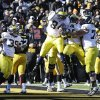 Photo - Michigan tight end A.J. Williams, center, celebrates with teammates after catching a 2-yard touchdown pass during the first half of an NCAA college football game against Iowa, Saturday, Nov. 23, 2013, in Iowa City, Iowa. (AP Photo/Charlie Neibergall)