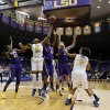 Photo - LSU and West Virginia basketball players fight for a rebound under the watchful eye of the tiger underneath the scoreboard in the second half of an NCAA college basketball second-round tournament game Tuesday, March 25, 2014, in Baton Rouge, La. LSU won 76-67. (AP Photo/Rogelio V. Solis)