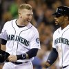 Photo -   Seattle Mariners' Mike Carp, left, smiles back at Eric Thames after the pair scored against the Boston Red Sox in the fourth inning of a baseball game Wednesday, Sept. 5, 2012, in Seattle. (AP Photo/Elaine Thompson)