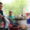 Photo - In this Tuesday, April 15, 2014 photo, worker Julliana Rojas, left, helps Mixteca Catering owner Paula Asuncion  to serve tamales with traditional Oaxacan mole sauce at the Lloyd Farmers Market in Portland, Oregon. Asuncion once worked in the fields, but after participating in a micro-business development program she now sells tamales throughout Portland and has even hired others to help in the business. (AP Photo/Gosia Wozniacka)