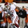 Juaquin Iglesias fights with Jacob Lacey on his back during the first half of the college football game between the University of Oklahoma Sooners (OU) and Oklahoma State University Cowboys (OSU) at Boone Pickens Stadium on Saturday, Nov. 29, 2008, in Stillwater, Okla. STAFF PHOTO BY BRYAN TERRY