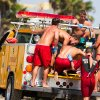 Photo - Lifeguards assist a person who was in the water and apparently struck by lightening Sunday July 27, 2014 in Los Angeles. Authorities said lightning struck 14 people, leaving two critically injured, as rare summer thunderstorms swept through Southern California on Sunday. (AP Photo/Steve Christensen)