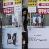Banners advertising Samsung Electronics\' Galaxy Note II and Apple\'s iPhone 5 are displayed on a door at a mobile phone shop in Seoul, South Korea Friday, Jan. 25, 2013. Samsung Electronics Co. said quarterly profit soared 76 percent, boosted by the popularity of its Galaxy smartphones, which outsold the iPhone for a fourth straight quarter. But the company said Friday it expects earnings to decline during the current quarter because of seasonally low demand for consumer electronics. (AP Photo/Ahn Young-joon)