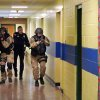 FILE - In this file photo of Jan. 28, 2013, members of the Washington County Sheriff\'s Office and the Hudson Falls Police Department use unleaded guns to take part in an emergency drill as they walk through a corridor inside the Hudson Falls Primary School in Hudson Falls, N.Y. School security has come under more scrutiny in the wake of the Sandy Hook Elementary School massacre in Newtown, Conn., that killed 26 people in December. (AP Photo/The Post-Star, Omar Ricardo Aquije, File)