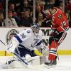 Photo - Tampa Bay Lightning goalie Ben Bishop, left, blocks a shot by Chicago Blackhawks' Jonathan Toews during the second period of an NHL hockey game in Chicago, Saturday, Oct. 5, 2013. (AP Photo/Nam Y. Huh)