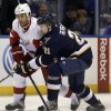 Detroit Red Wings\' Todd Bertuzzi, left, passes the puck around St. Louis Blues\' Patrik Berglund, of Sweden, during the first period of an NHL hockey game Thursday, Feb. 7, 2013, in St. Louis. (AP Photo/Jeff Roberson)