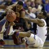 Photo - Eastern Kentucky's Corey Walden, left, and Kansas' Andrew Wiggins get tangled up while chasing after a loose ball during the first half of a second-round game in the NCAA college basketball tournament Friday, March 21, 2014, in St. Louis. (AP Photo/Jeff Roberson)