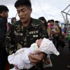 A soldier carries one-day-old baby Ian Daniel Honrado to a waiting military transport plane Wednesday Nov. 13, 2013 from the damaged Tacloban airport at Tacloban city, Leyte province in central Philippines. Typhoon Haiyan, one of the strongest storms on record, slammed into central Philippine provinces Friday, leaving a wide swath of destruction and thousands of people dead. (AP Photo/Bullit Marquez)