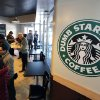 Photo - People wait at Dumb Starbucks coffee in Los Angeles Monday, Feb. 10, 2014.  The store resembles a Starbucks with a green awning and mermaid logo, but with the word