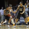 Photo - Vanderbilt guard Christina Foggie (10) collides with Tennessee guard Andraya Carter, center, as Vanderbilt forward Rayte'a Long (44) looks on in the first half of an NCAA college basketball game, Monday, Feb. 10, 2014, in Knoxville, Tenn. (AP Photo/Wade Payne)