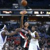 Portland Trail Blazers\' Damian Lillard (0) shoots between Sacramento Kings defenders John Salmons, left, and Jason Thompson, right, during the first half of an NBA basketball game in Sacramento, Calif., on Sunday, Dec. 23, 2012. (AP Photo/Steve Yeater)