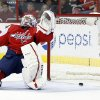 Photo - Washington Capitals goalie Braden Holtby (70) falls backwards as the puck bounces out after a goal by Ottawa Senators center Kyle Turris in the second period of an NHL hockey game, Tuesday, Jan. 21, 2014, in Washington. (AP Photo/Alex Brandon)