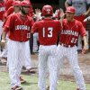 Photo - Louisiana-Lafayette's Caleb Adams (13) celebrates with teammates Nick Zaunbrecher (33) and Matt Hicks (26) after scoring on an RBI by Seth Harrison (not shown) in the fifth inning during an NCAA college baseball tournament regional game against San Diego State in Lafayette, La., Saturday, May 31, 2014. Louisiana-Lafayette won 9-2. (AP Photo/Jonathan Bachman)