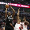 Brooklyn Nets guard Joe Johnson (7) shoots over Chicago Bulls\' Jimmy Butler (21) and Nazr Mohammed during the first half of Game 3 of their first-round NBA basketball playoff series, Thursday, April 25, 2013, in Chicago. (AP Photo/Charles Rex Arbogast)