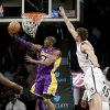 Los Angeles Lakers\' Kobe Bryant, left, puts up a shot underneath the basket while Brooklyn Nets\' Brook Lopez defends during the first half of the NBA basketball game at the Barclays Center Tuesday, Feb. 5, 2013 in New York. (AP Photo/Seth Wenig)