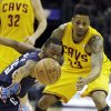 Photo - Charlotte Bobcats' Kemba Walker, front left, knocks the ball away from Cleveland Cavaliers' Alonzo Gee (33) in the second quarter of an NBA basketball game on Saturday, April 5, 2014, in Cleveland. (AP Photo/Mark Duncan)