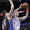 Orlando Magic center Nikola Vucevic (9) defends as Oklahoma City Thunder\'s Nick Collison (4) goes up for the basket during the fourth quarter of an NBA basketball game in Oklahoma City, Friday, March 15, 2013. Oklahoma City won 117-104. (AP Photo/Alonzo Adams)