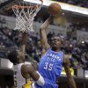 Oklahoma City Thunder forward Kevin Durant, right, goes up for a dunk over Indiana Pacers center Roy Hibbert in the first half of an NBA basketball game in Indianapolis, Friday, April 6, 2012. (AP Photo/Michael Conroy) ORG XMIT: NAF102