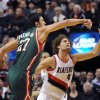 Photo - Milwaukee Bucks center Zaza Pachulia (27) knocks the ball away from Portland Trail Blazers center Robin Lopez (42) during the first half of an NBA basketball game in Portland, Ore., Tuesday, March 18, 2014. (AP Photo/Steve Dykes)