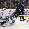 Photo - Vancouver Canucks' Jason Garrison (5) is hit by Winnipeg Jets' Andrew Ladd (16) as he jumps to avoid a shot during the second period of an NHL hockey game in Winnipeg, Manitoba, on Friday, Jan. 31, 2014. (AP Photo/The Canadian Press, John Woods)