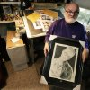 Artist Michael Reagan holds a portrait he drew of Sgt. Christopher Wrinkle, a U.S. Marine dog handler who died along with his dog Tosca, who is also shown in the portrait, in 2011 as a result of a living-quarters fire in Afghanistan, Thursday, Oct. 4, 2012 at his home in Edmonds, Wash. Since starting the Fallen Heros Project in 2004, Reagan has drawn more than 3,000 portraits and given them free-of-charge to families of fallen soldiers. On the table behind him are family photos that are to be used by Reagan for upcoming portraits. (AP Photo/Ted S. Warren)