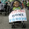 Photo - Jericho Biffel, 2, holds a sign welcoming troops home during the annual St. Patrick's Day Parade in downtown Oklahoma City, Saturday, March 17, 2012. Jericho's father, Jerry Biffel, is deployed with the 45th Infantry Brigade Combat Team and will be returning from Afghanistan. Photo by Bryan Terry, The Oklahoman