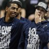 Photo - Connecticut's Shabazz Napier, right, reacts as his name is revealed on the Huskies Wall of Honor as coach Kevin Ollie, left, looks over at Napier during a pep rally celebrating Connecticut's fourth NCAA men's basketball championship Tuesday, April 8, 2014, in Storrs, Conn. (AP Photo/Jessica Hill)
