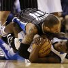 Dallas Mavericks\' Darren Collison, bottom, and Orlando Magic guard Jameer Nelson, top, wrestle for control of a loose ball in the second half of an NBA basketball game Wednesday, Feb. 20, 2013, in Dallas. Nelson later left the game with a left leg injury. The Mavericks won 111-96. (AP Photo/Tony Gutierrez)