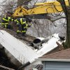 South Bend firefighters use an ax Monday, March 18, 2013, along Iowa Street in South Bend, Ind., as they prepare to remove a part of the roof of a home hit by a jet on Sunday. Two people were killed. (AP Photo/South Bend Tribune, James Brosher)