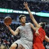 Houston Rockets\' Chandler Parsons (25) looks to pass around Chicago Bulls\' Joakim Noah (13) during the first quarter of an NBA basketball game in Chicago, Tuesday, Dec. 25, 2012. (AP Photo/Paul Beaty)