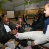 NBA BASKETBALL PLAYER: Oklahoma City Thunder guard Damien Wilkins puts a new pair of Adidas tennis shoes on the feet of a student at Dunbar Elementary School on Monday. ORG XMIT: 0812152153543589