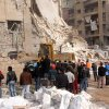 This photo released by the Syrian official news agency, SANA, shows rescue workers and bystanders at a building damaged by a rocket attack, that killed at least 12 people, in Aleppo, Syria, Friday, Jan. 18, 2013. In a spike in civil war violence that Syrian state media blamed on rebel fighters a rocket attack in the northern city of Aleppo occurred during a particularly bloody week nearly two years after an uprising began against Assad\'s regime. (AP Photo/SANA)