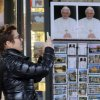 A woman takes photos next to portraits of Pope Benedict XVI, outside a bookshop near the Vatican, Tuesday, Feb. 26, 2013. Pope Benedict XVI will be known as