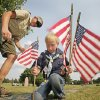 Cub Scout leader Frank Sherman and Bear Logan Weber place flags on veterans graves in Edmond\'s Memorial Park Cemetery for Memorial Day, Thursday, May 24, 2012. Photo By David McDaniel/The Oklahoman