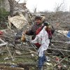 Lisa Lyons recovers personal items from debris for her friend whose house was damaged Friday after a tornado hit the village of Moscow, Ohio, Sunday, March 4, 2012. (AP Photo/David Kohl) ORG XMIT: OHDK109