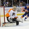 Photo - New York Islanders center Peter Regin (16) watches the puck shot by Frans Nielsen fly past Philadelphia Flyers goalie Steve Mason (35) to score in the second period of an NHL hockey game at the Nassau Coliseum on Saturday, Oct. 26, 2013, in Uniondale, N.Y. (AP Photo/Kathy Kmonicek)